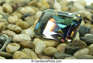 Emerald cut faceted mystic topaz gemstone on a bed of rocks