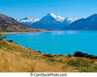 Mighty Aoraki Mount Cook towering over glacial Lake Pukaki in hues of turquoise from silt, Aoraki Mount Cook National Park, Canterbury, South Island, New Zealand