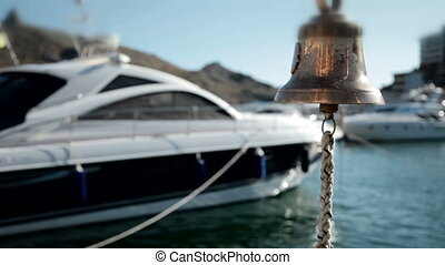 Bell in emergency on a background of yachts