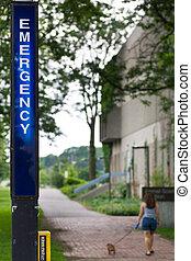 Emergency call box and woman walking dog
