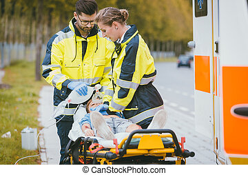 Emergency doctor giving oxygen to accident victim