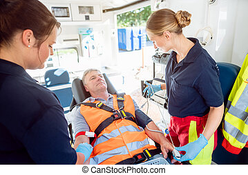 Emergency doctor in ambulance talking to injured man