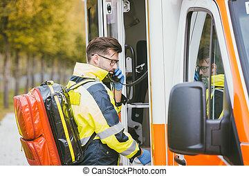 Emergency doctor using radio of ambulance