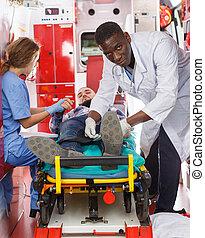 Emergency doctors fixing patient on stretcher