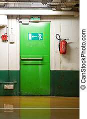 Green emergency exit door. French sign above the door and red fire extinguisher to the right.