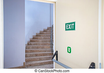Emergency exit door with exit sign. Exit up the stairs. Fire escape in a modern building.