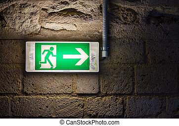 emergency exit light green sign on brick wall in the dark