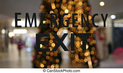 Emergency exit sign on empty city mall during pandemic