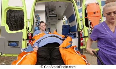 Emergency medical ambulance service paramedics crew fixing...