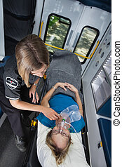 Senior woman in ambulance receiving emergency medical care