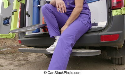 Emergency medical service stressed paramedic in front of ambulance