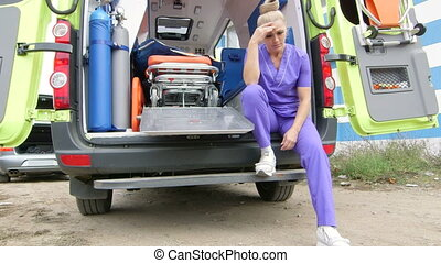 Emergency medical service upset tired paramedic sitting in...