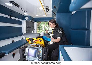 Emergency Medical Technician - EMT worker listening to heart...