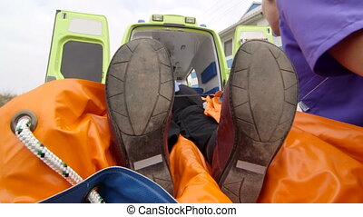 Emergency medical technicians and paramedics loading patient...