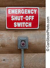 Emeregency shut-off button and sign near a hazardous machine.