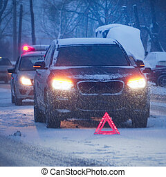 Emergency sign in front of the car on evening winter road