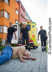 Emergency team assisting unconscious man on street