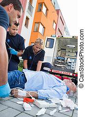 Emergency team examining injured patient on street