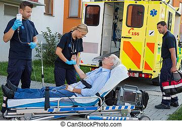 Emergency team examining patient on stretcher
