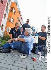 Emergency team helping injured patient on street
