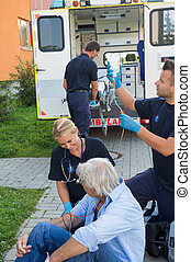 Emergency team treating injured patient on street -...