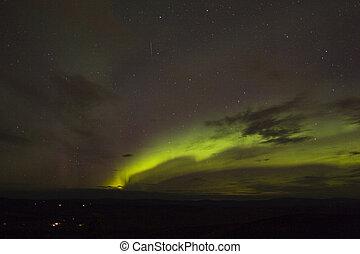 Emerging aurora arc with meteor