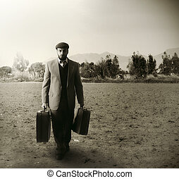 Emigrant man with the suitcases in an agricultural field