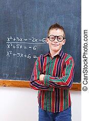 Eminent boy at chalkboard - Eminent math boy in glasses,...