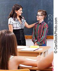 Eminent boy at chalkboard - Teacher praise eminent math boy...