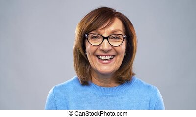 portrait of happy senior woman in glasses - emotion, age and...