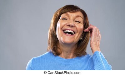 portrait of happy senior woman laughing - emotion, age and...