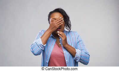 scared african american woman over grey background -...