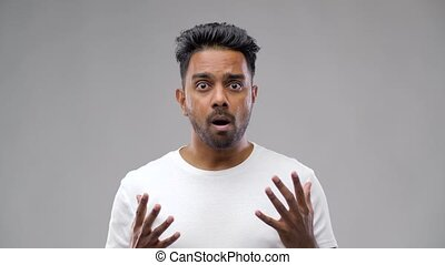 shocked indian man over grey background - emotion,...