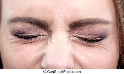 Emotion girl screwing up her blue eyes. Close up - Emotion...