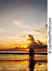 Silhouette lovers relax on the beach in color of sunset