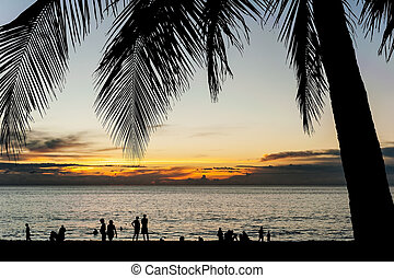 Silhouette people relax on the beach with color of sunset