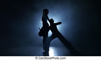 Emotional and graceful latinamerican dance performed by champions in smoky studio illuminated with white spotlight, dressed in luxurious costumes, couple man and girl emotionally posing isolated on black background, silhouette
