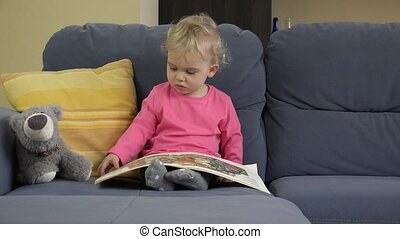 Emotional baby girl turn pages of book sitting on sofa with teddy bear friend