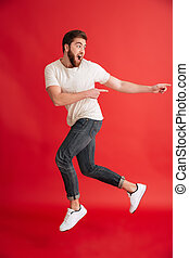 Emotional bearded man jumping pointing to copyspace.