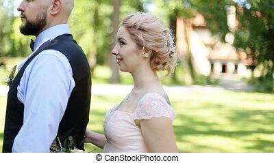 Emotional beautiful bride hugging newlywed groom from behind...