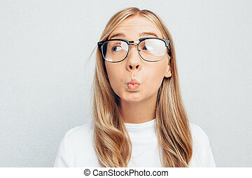 Emotional beautiful girl with glasses, in a white t-shirt,...