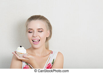 Emotional blonde model enjoying sweet dessert with butter cream. Space for text