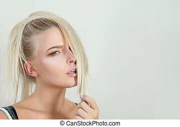Emotional blonde model with pink lips and beautiful blue eyes looking into the camera. Empty space