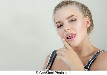 Emotional blonde woman with perfect makeup showing tongue. Space for text