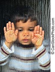 Emotional boy - A little sad kid looking through glass