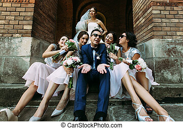 Emotional bride with a groom and the beautiful bridesmaids