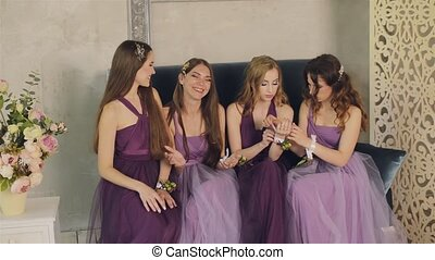Emotional bridesmaids look at the boutonniere on their hands, talking and laughing during the morning of the bride in a photo studio. Girls in purple wedding dresses sitting on the studio couch.