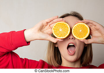 Emotional brunette girl posing with a half orange, covering eyes, against white wall. Space for text