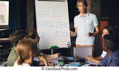 Emotional business teacher is making presentation for corporate students talking and pointing at whiteboard while company employees are listening and laughing.