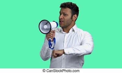 Emotional businessman talking into megaphone. Young dark-skinned man in white shirt speaking in loudspeaker on color background.